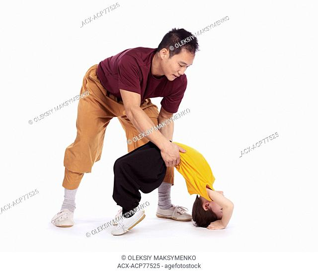 Martial art instructor helping a child to hold a bridge stand isolated on white background