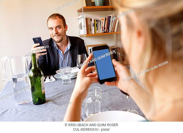 Mid adult couple at home, sitting at dinner table, using smartphones