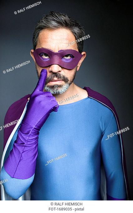 Portrait of confident superhero gesturing against gray background