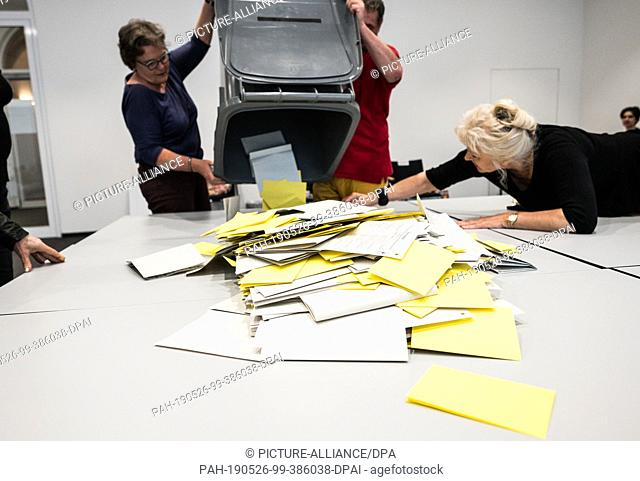 26 May 2019, Hessen, Wiesbaden: After the polling station in the town hall closes, election workers tip their ballot papers onto a counting table