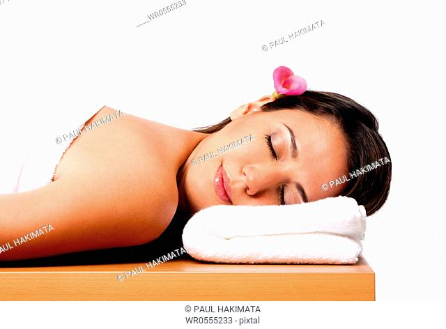 Beautiful happy peaceful sleeping woman at a spa, laying on wooden massage table with head on pillow wearing a towel and pink Calla Lilly flower in hair
