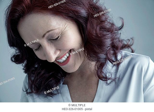 Portrait Caucasian mature woman with curly burgundy red hair laughing with eyes closed