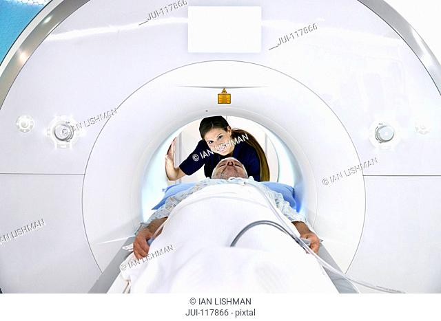 Hospital Radiographer With Male Patient Operating MRI Scanner