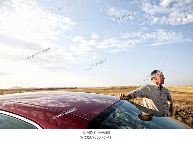 Portrait of a senior Caucasian man and his car parked along a highway in eastern Washington State, USA