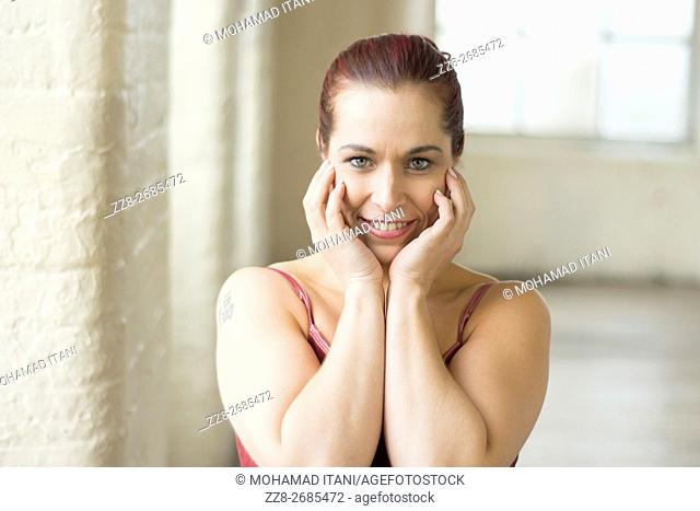 Happy woman hands touching face indoors smiling