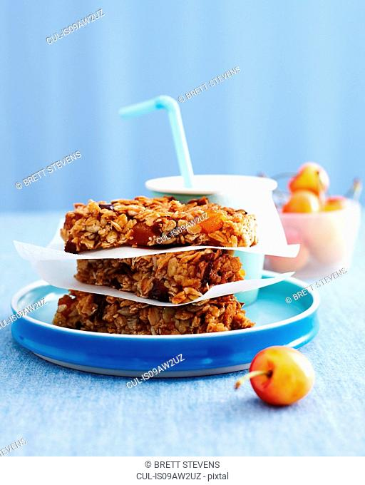 Stack of muesli flapjacks, drink with bowl of cherries, kids lunch idea