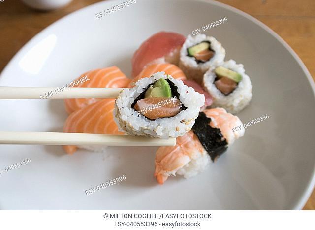 Fresh salmon and avocado uramaki sushi between chopsticks with salmon nigiri, prawn nigiri and tuna nigiri in the background