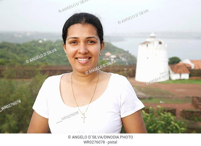 Lady smiling , Lighthouse of Fort Aguada in background , Goa , India MR468