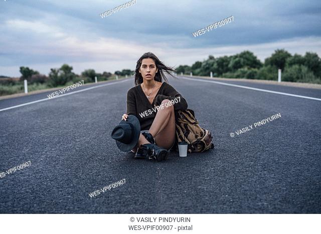 Portrait of hitchhiking young woman with backpack and beverage sitting on lane