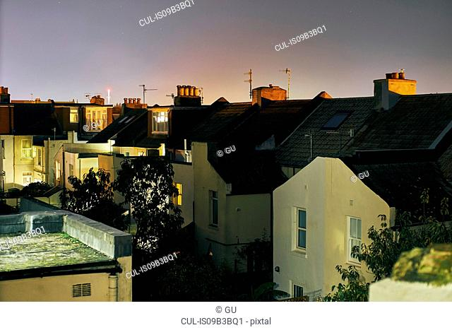 Elevated view of a row of terraced house roof tops at night, Brighton, East Sussex, England