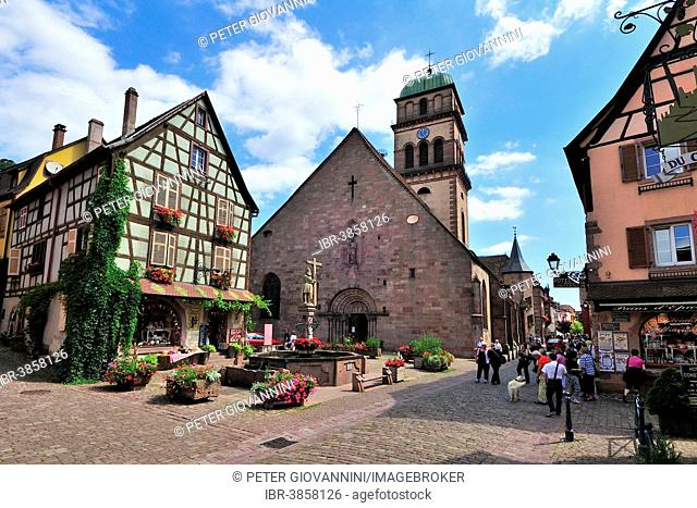 Half-timbered house and fountain in front of the Church of Sainte-Croix on the Rue du Général de Gaulle, Kaysersberg, Alsace, Haut-Rhin, France