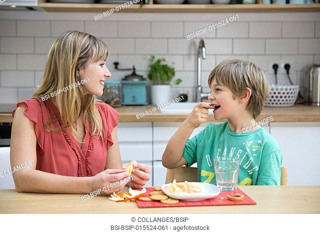 A child having his afternoon snack with his mother