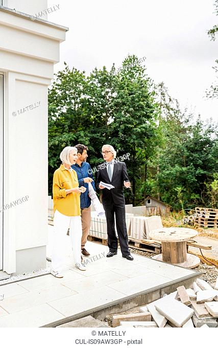Full length view of couple discussing housing redevelopment with architect