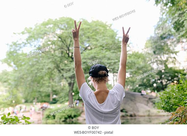 Rear view of young woman at lakeside in park with raised arms