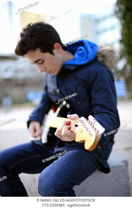 Exterior portrait of teenager playing the electric guitar