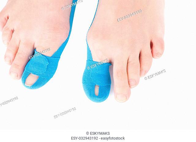 Therapeutic tape on female toe isolated on white background. Chronic pain, alternative medicine. Rehabilitation and physiotherapy