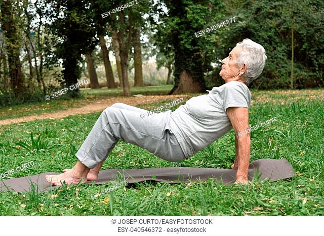 elderly woman practicing yoga outdoors