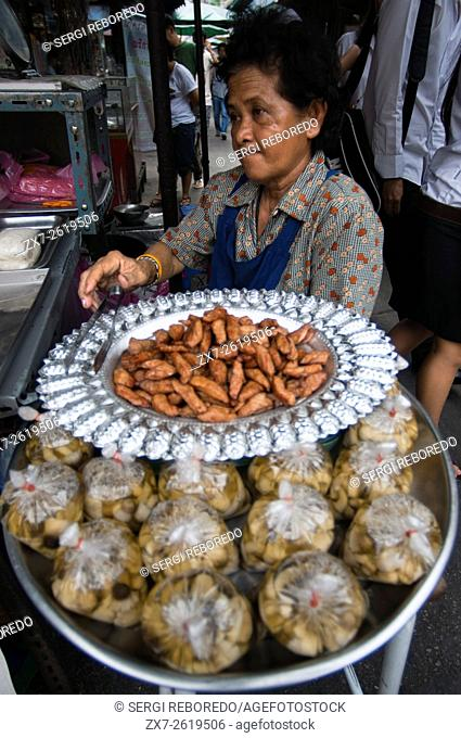 Woman selling pring rolls. Bangkok's Chinatown, Thailand. Market stall and street food being prepared in Chinatown Bangkok, Thailand