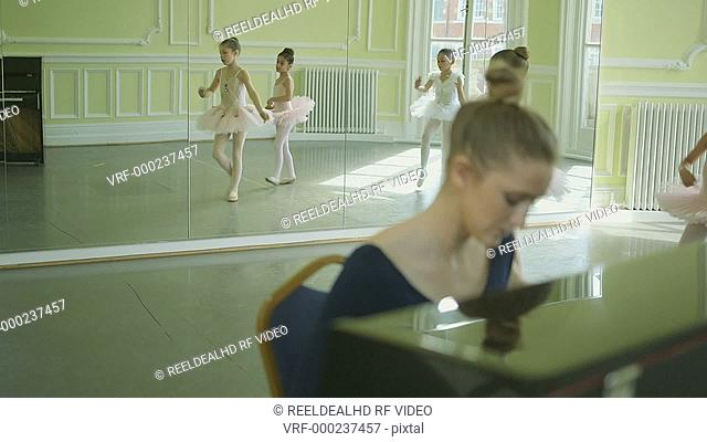 Female Ballet Dancer plays the piano in the foregound whilst instructing three young Ballerinas on their movements as they twirl and glide through the Studio in...
