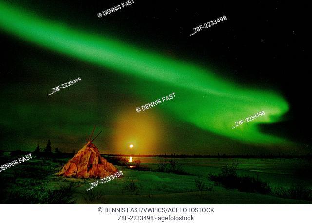 Aurora Borealis Northern Lights full moon over wigwam caribou skin tepee near Churchill, Manitoba, sub-arctic, Hudson Bay, Northern Canada