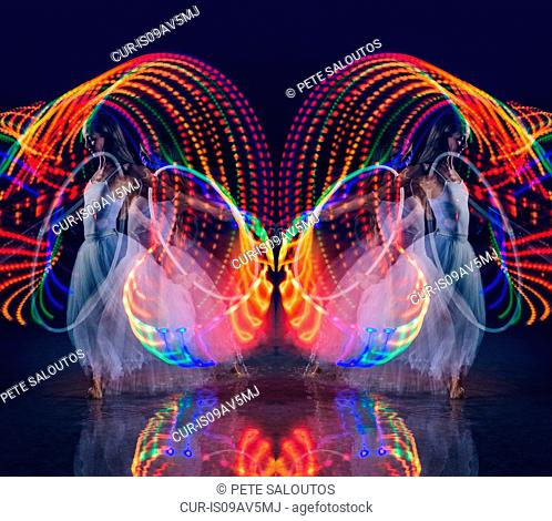 Symmetrical composite of woman dancing with illuminated multi-coloured hoop at night