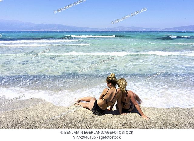 best friends, two relaxed girls sitting together in bikini on beach and enjoying seaside. Dutch ethnicity. At holiday destination Chrissi Island, Crete, Greece