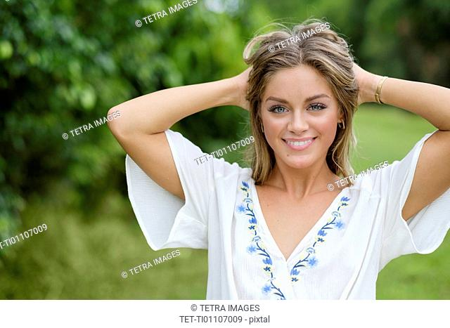 Smiling young woman with hands in her hair