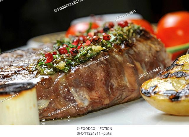 Grilled beef with herb butter and red peppercorns