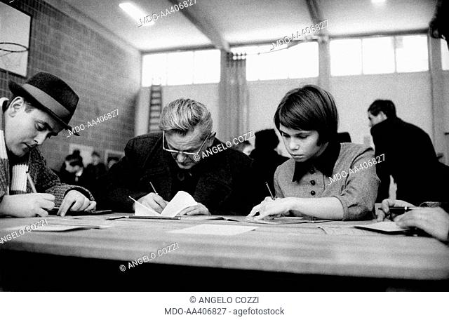 A girl helping a man in the filling of the form for his pass. German student helping a man in the filling of the form for his East Berlin pass