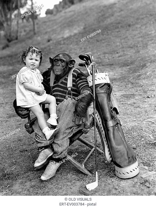 Monkey with golf clubs and toddler girl All persons depicted are not longer living and no estate exists Supplier warranties that there will be no model release...