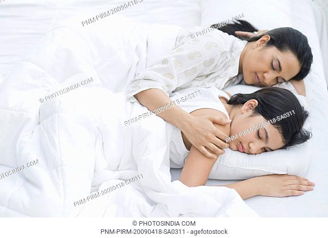 Woman sleeping with her daughter