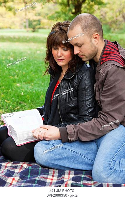 couple reading bible and praying together in the park, edmonton alberta canada