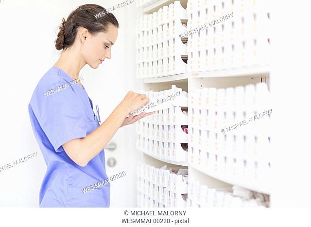 Dental assistant at shelf looking for dental imprint