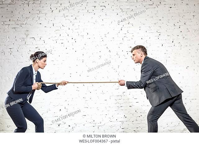 Businessman and businesswoman having tug-of-war