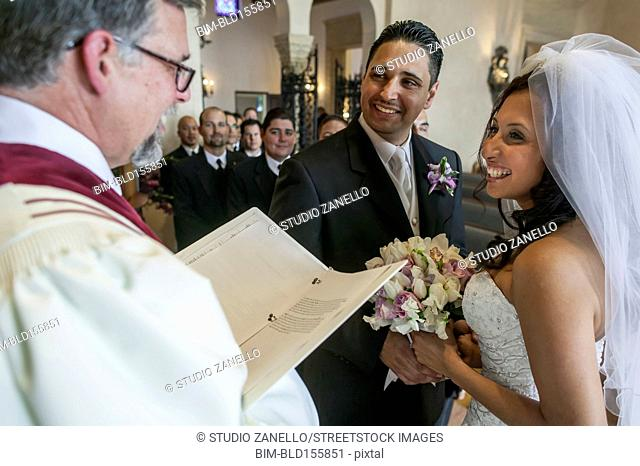 Priest reading to bride and groom during wedding ceremony