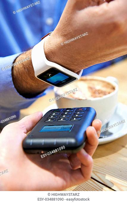 Man Paying In Coffee Shop Using Contactless Payment App On Smart Watch