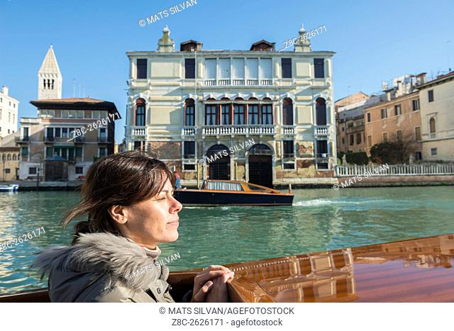 Woman travel in a taxi boat on Grand Canal in Venice, Italy