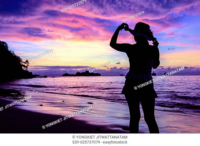 Beautiful landscape of colorful summer sky during sunrise and silhouette girl in a swimwear poses on the beach at Miang island in Mu Koh Similan National Park