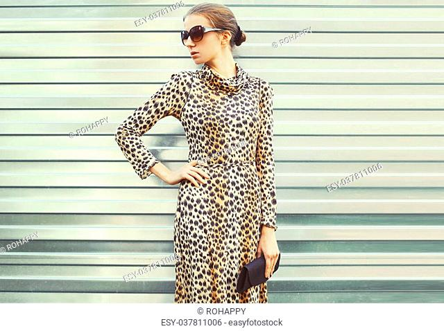 Fashion pretty woman in sunglasses and leopard dress with handbag clutch over metal background, view profile