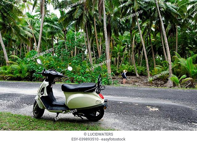 AITUTAKI - SEP 20:Tourist woman explore the nature with motorbike on Sep 20 2013.It's one of the must popular activity in the Island but Cook Islands Driver's...