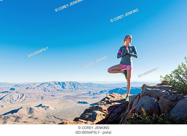 Young female trail runner doing yoga pose on Pacific Crest Trail, Pine Valley, California, USA