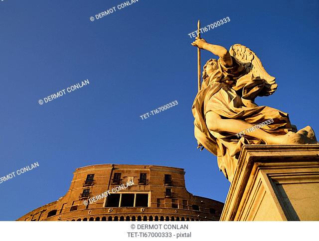 Statue of angel and Castle Sant' Angelo against clear sky