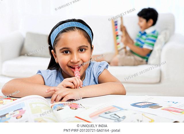Girl reading books with her brother in the background