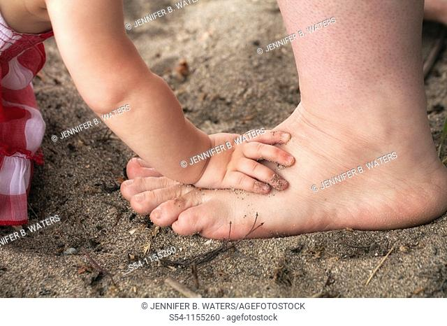 A baby puts her hand on her mothers foot at the beach