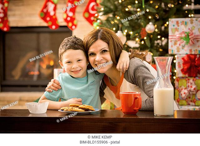 Caucasian mother and son leaving cookies and milk for Santa at Christmas