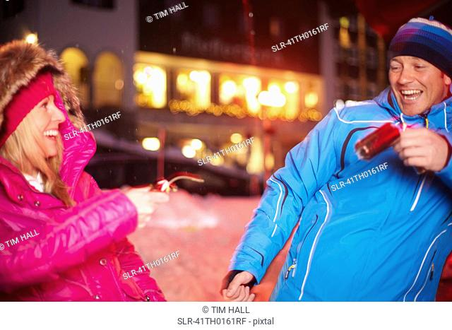Couple pulling Christmas cracker in snow