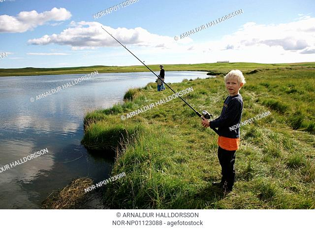 A boy fishing near the river and looking at the camera