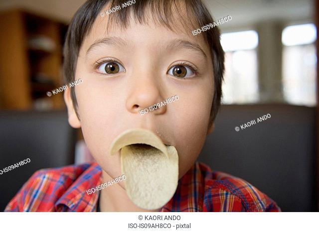 Boy imitating bird beak with crisps