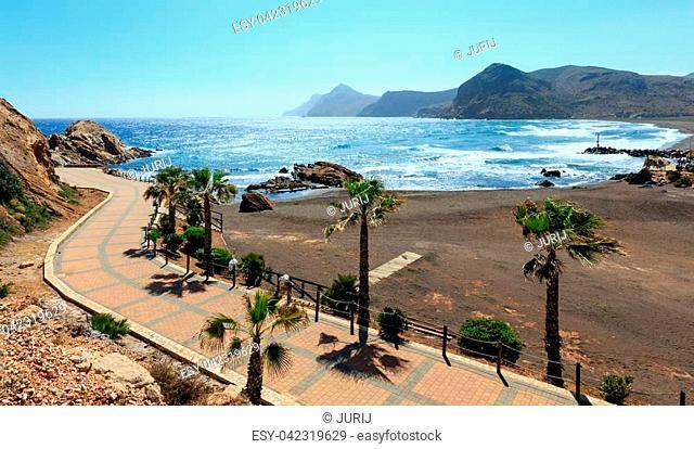 Mediterranean sea summer coastline view with beach, footpath and palm trees (Portman bay, Costa Blanca, Spain). People are unrecognizable