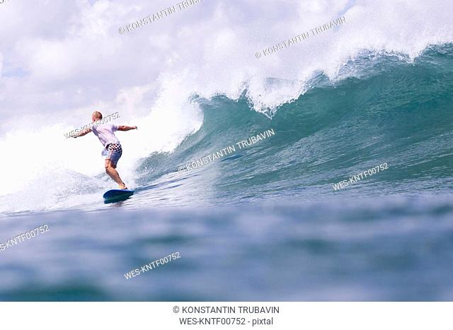 Indonesia, Bali, man surfing on a wave